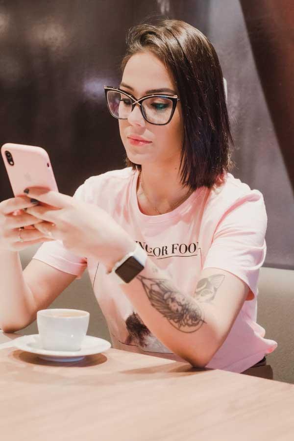 Joven-atractiva-con-tatuaje-sostiene-un-telefono-movil-entrada-de-blog-Unsplash